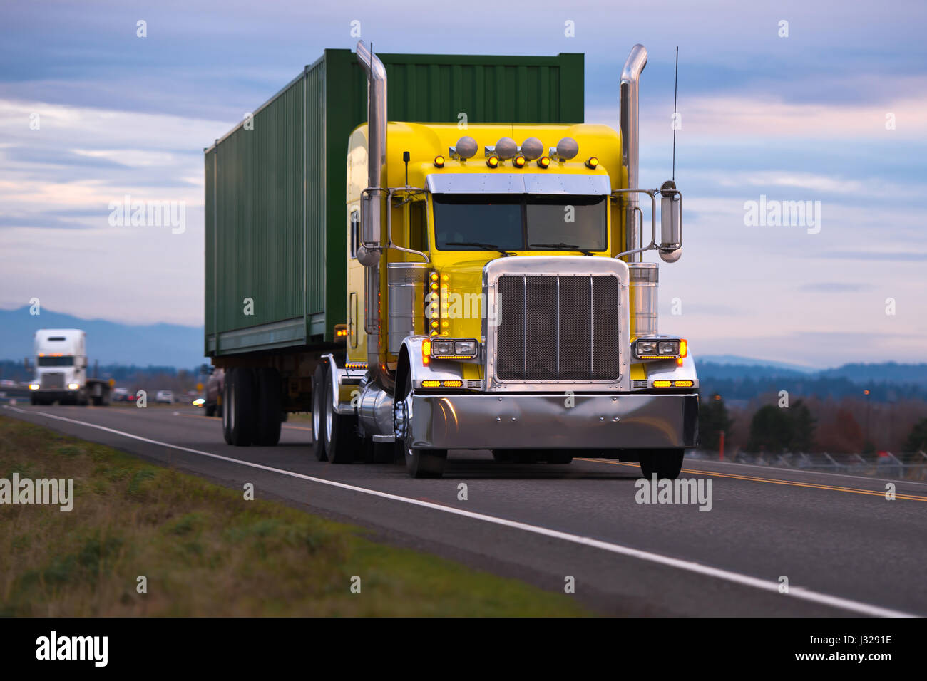 Classic American powerful yellow big rig semi truck with high chrome tailpipes powerful headlights and green container - Stock Image