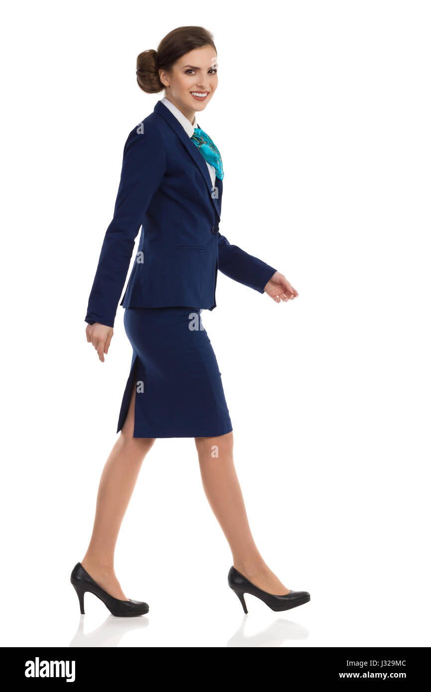 Beautiful young woman in blue suit, skirt and black high heels walking and looking at camera. Side view. Full length - Stock Image