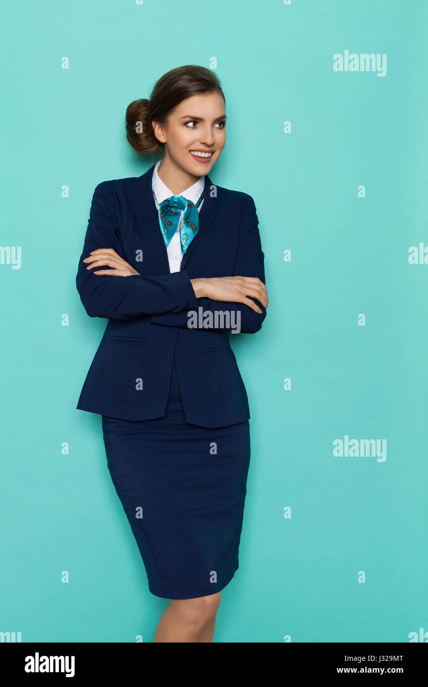 Smiling young woman in blue suit and turquoise scarf standing with arms crossed and looking away. Three quarter - Stock Image