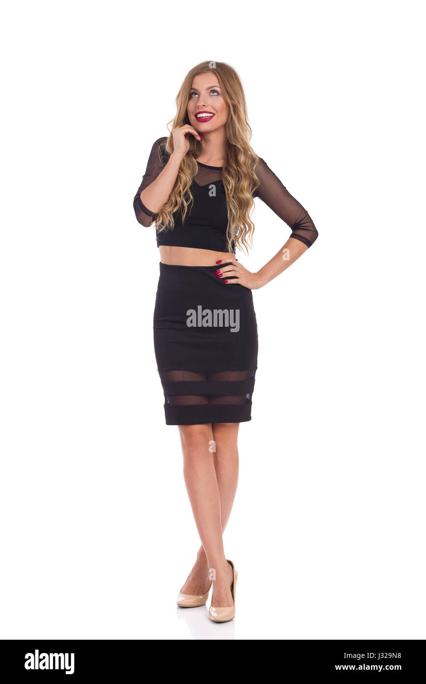 Beautiful smiling blond young woman in black dress standing with legs crossed, holding hand on chin and looking - Stock Image