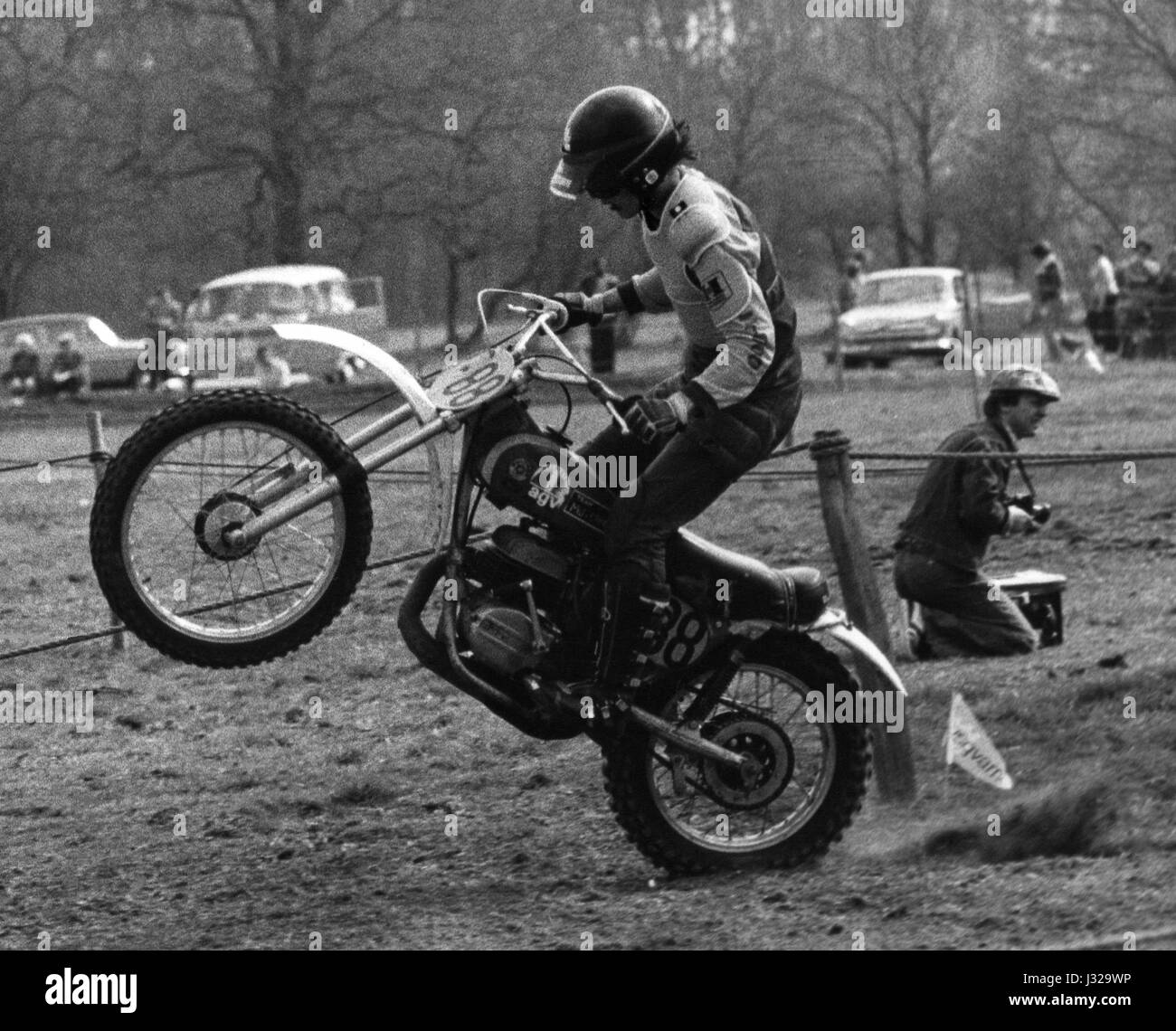 A rider performs a wheelie while competing in a motorcycle scrambling event at  Crawley in Sussex, England on April Stock Photo