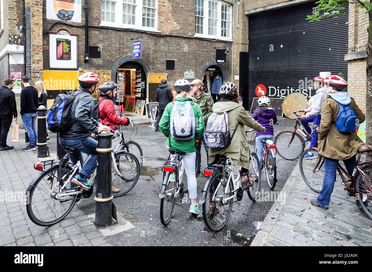 Tourists on a bike tour of London listed to their guide in London's Brick Lane, a popular tourist destination in Stock Photo