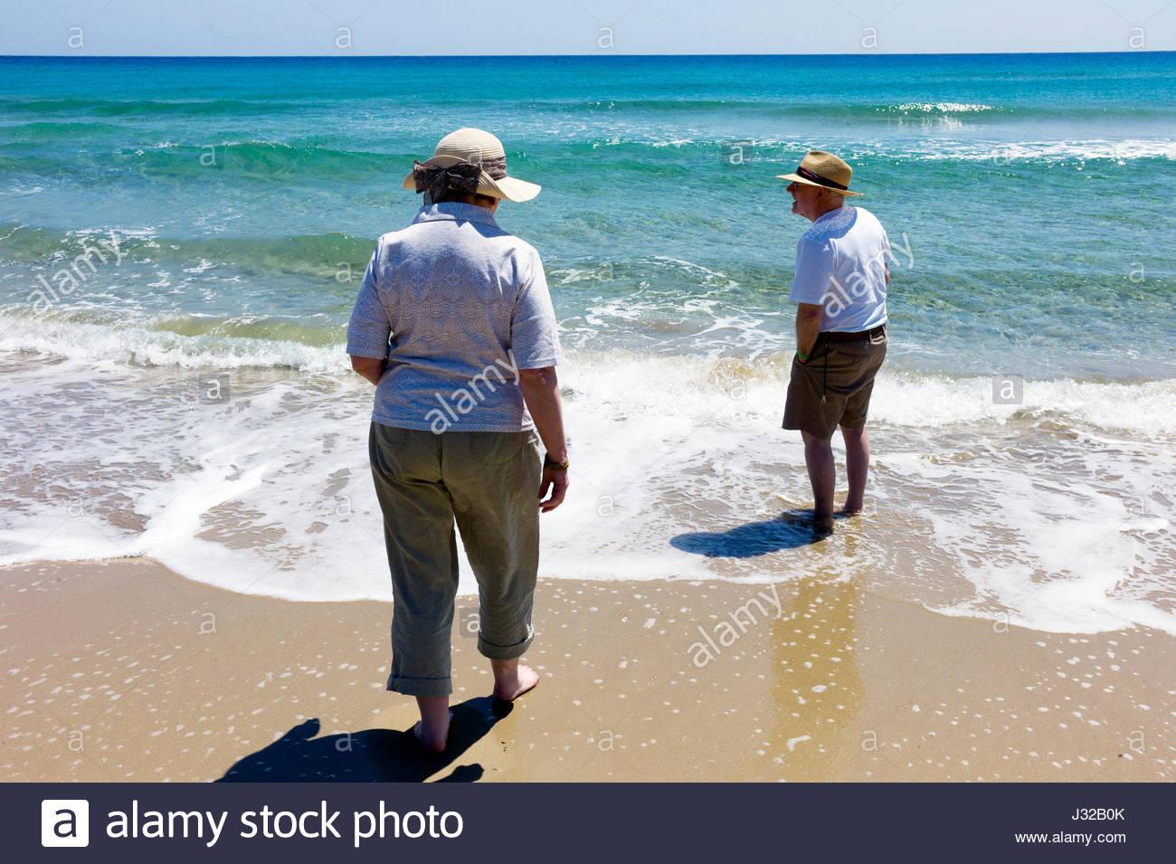Senior man and woman tourists paddling in the Mediterranean Sea at Golden Sand Beach on the Karpasian Peninsula, Stock Photo