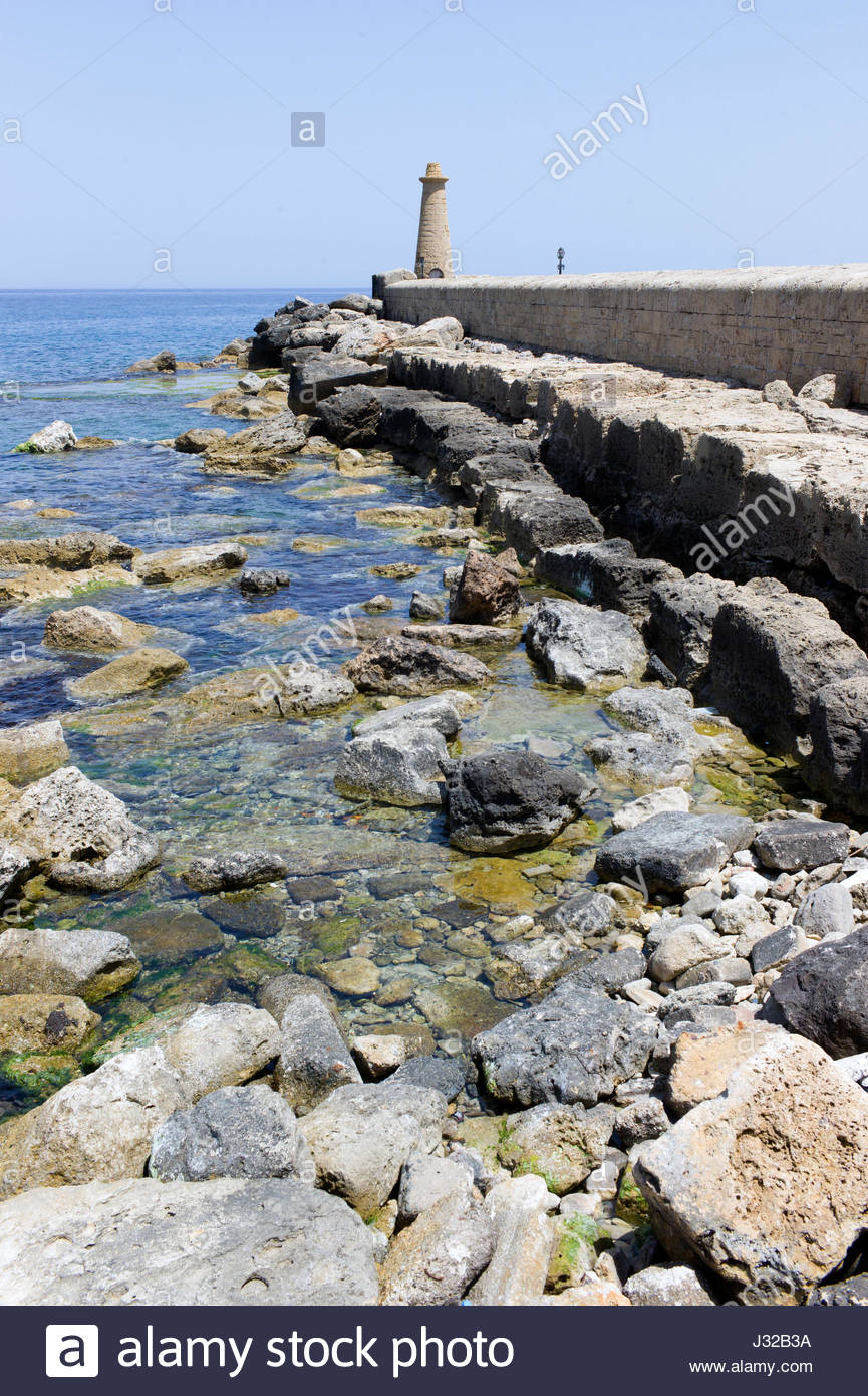 The rocky shore line, harbour wall and lighthouse, Kyrenia, northern Cyprus Stock Photo