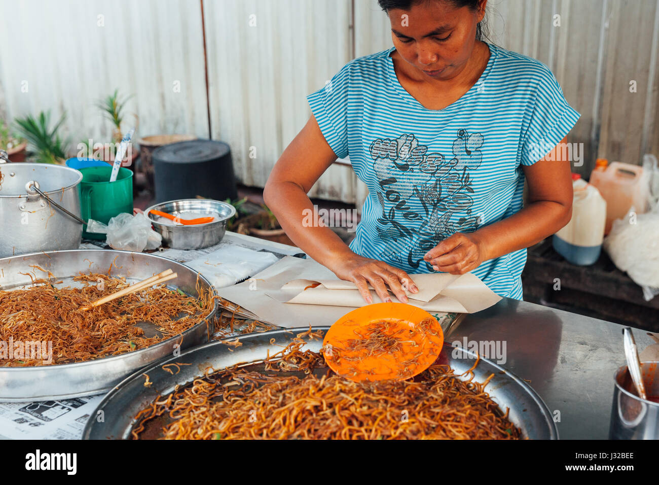 GEORGE TOWN, MALAYSIA - MARCH 23: Woman packing stir-fried noodles into the paper at Kimberly Street Food Night - Stock Image