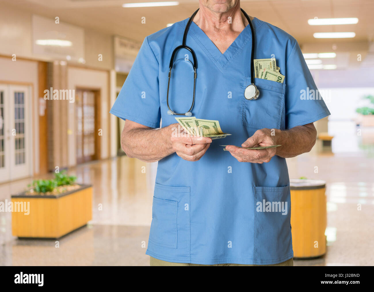 Doctor in scrubs in hospital counting money  - healthcare, health insurance, medical bills concept - Stock Image