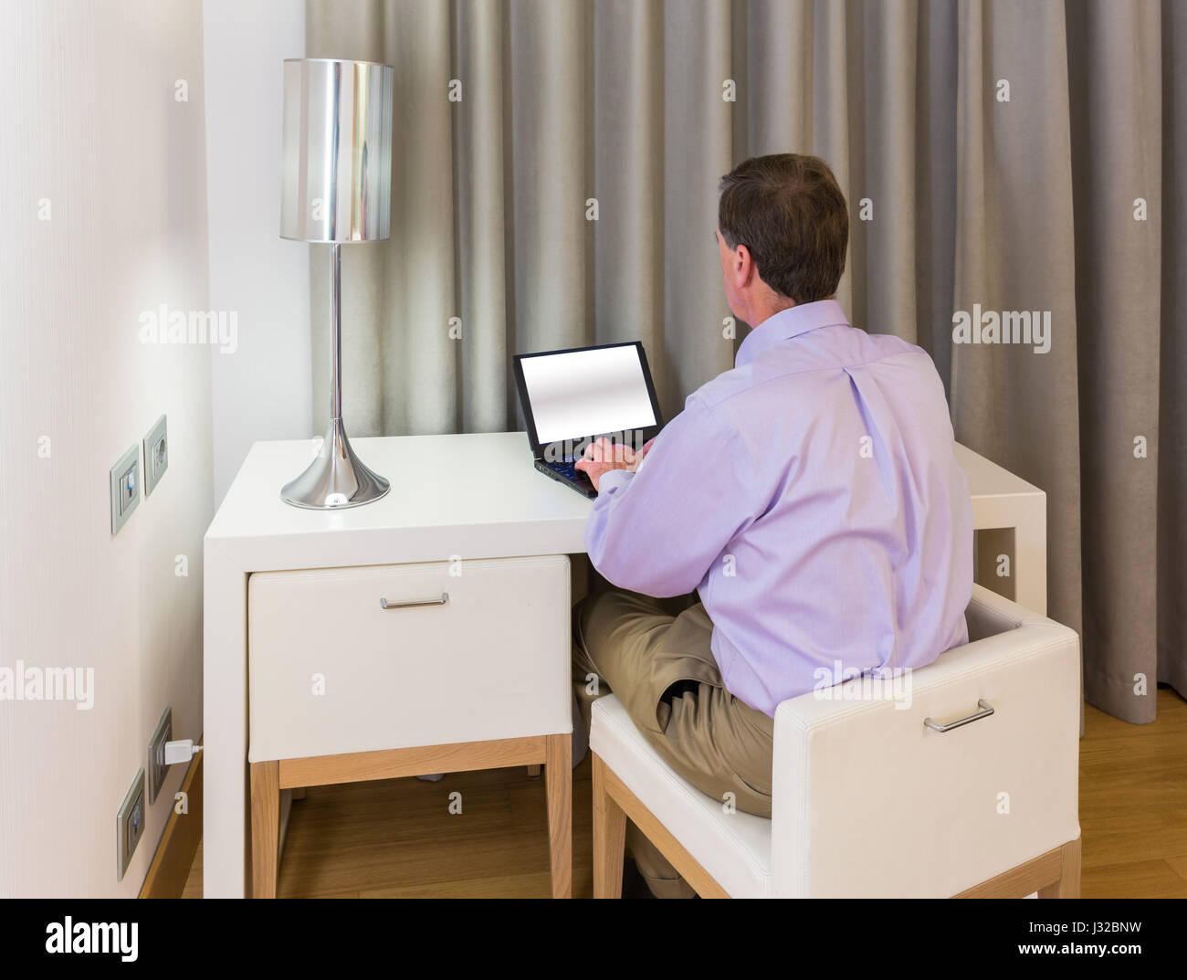 Senior businessman in hotel room sitting at a white table desk working on his laptop in the evening Stock Photo