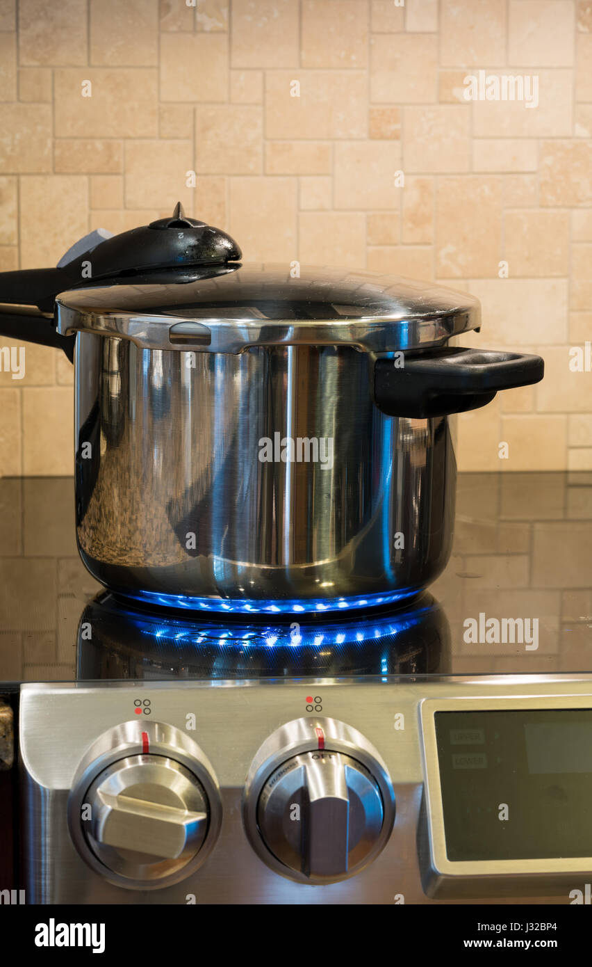 Pressure cooker letting off steam on a modern induction cooking hob - Stock Image
