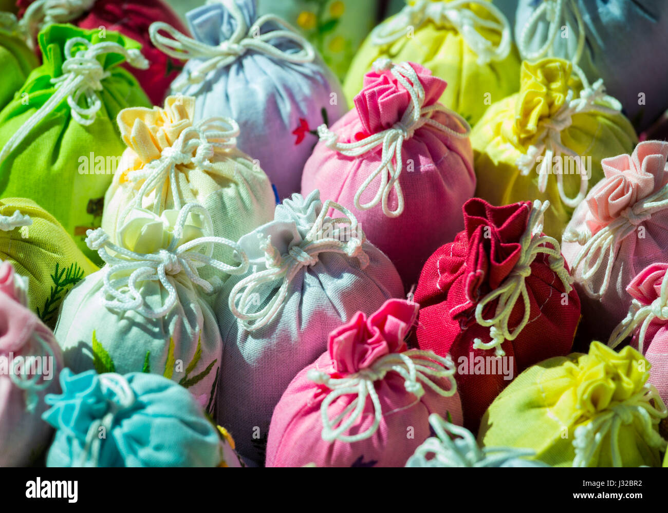 Colorful lavender bags in embroidered gift cloth sacks tied with string - Stock Image