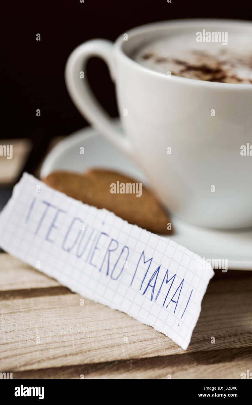 closeup of a piece of paper with the text te quiero mama, I love you mom written in spanish, next to a cup with - Stock Image