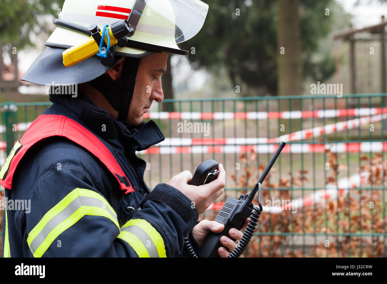 German firefighter leader used a walkie talkie in action - Stock Image
