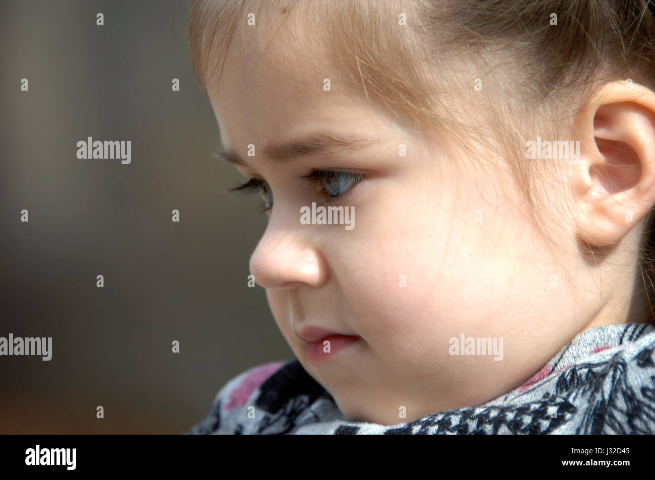 Lost in thought, this little girl is in profile and close up.  She is resting her chin on her chest. - Stock Image