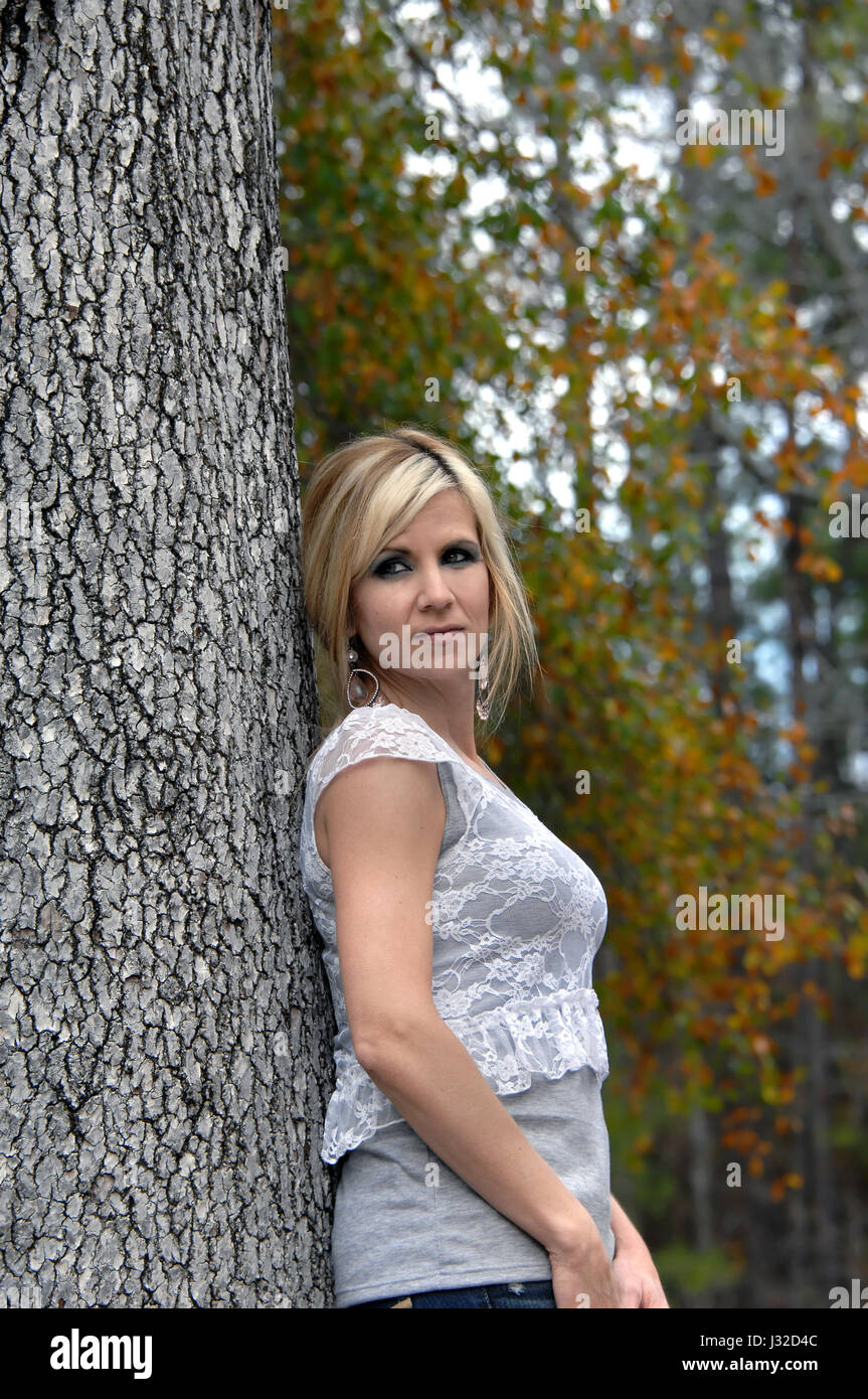 Arkansas leaves surround young woman as she leans against tree trunk.  She is wearing a grey T shirt with lacy over - Stock Image