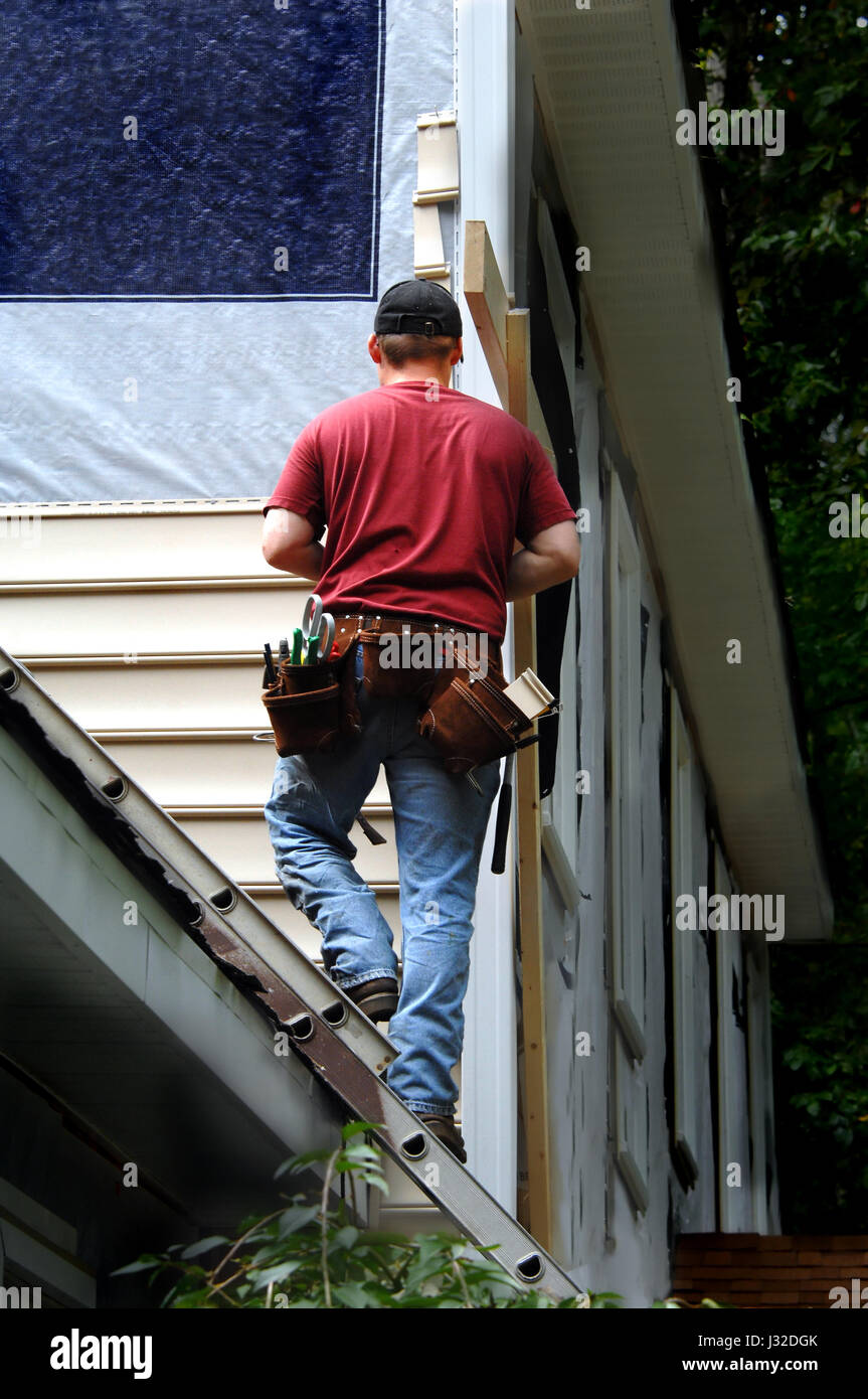 Homeowner does a self installment job on his home siding.  He is standing on a ladder attached to the roof of his - Stock Image
