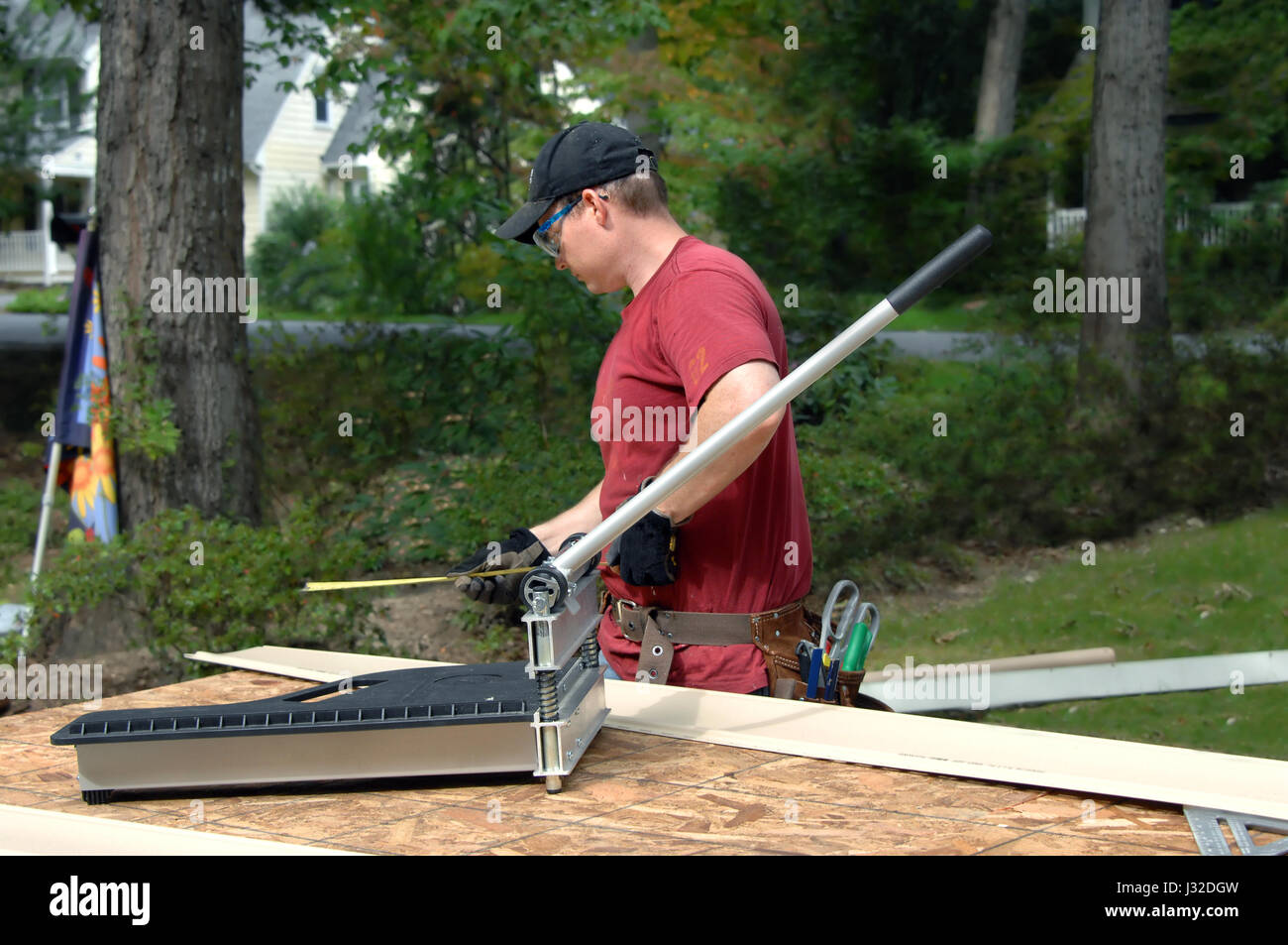 Young man works to put siding on his home.  He is using a tape measure to check accuracy of his cut.  His is wearing - Stock Image