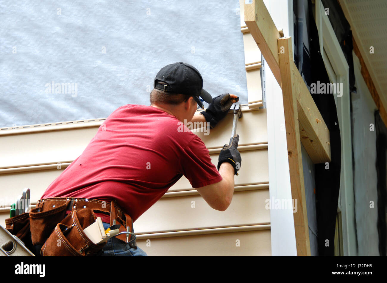 Young homeowner installs siding to his home.  He is holding a hammer and wearing a tool belt. - Stock Image