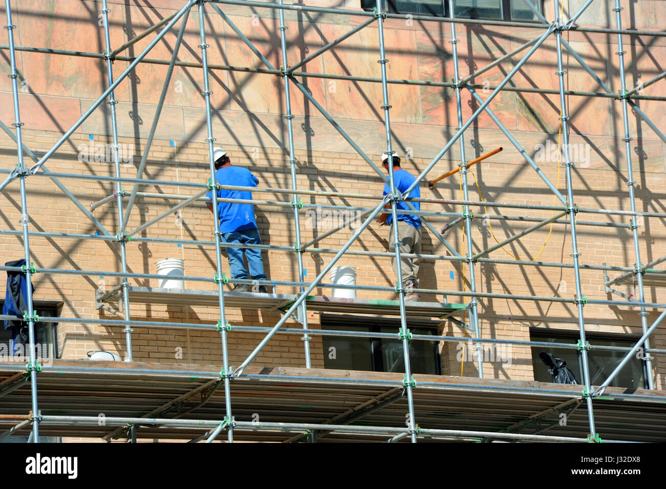 Two men stand on scaffolding and work on exterior repairs on the City Building in downtown, Asheville, North Carolina. - Stock Image