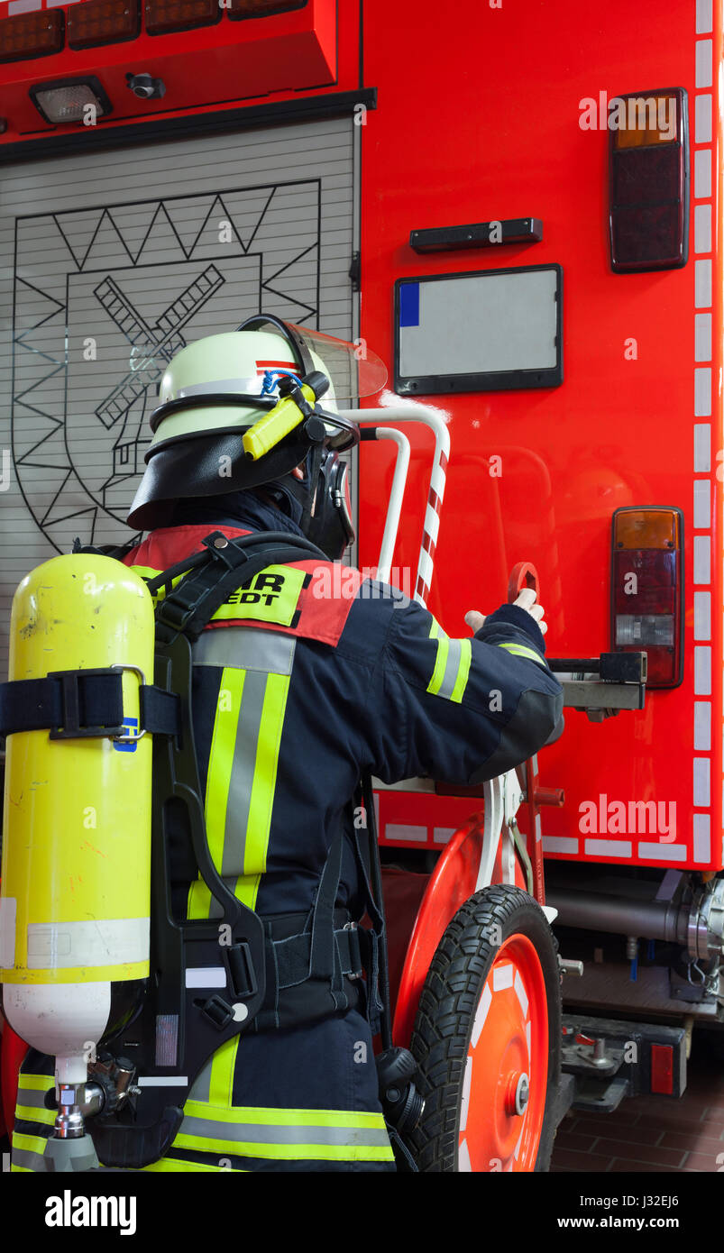 German firefighter in action with oxygen tank and mask - Stock Image