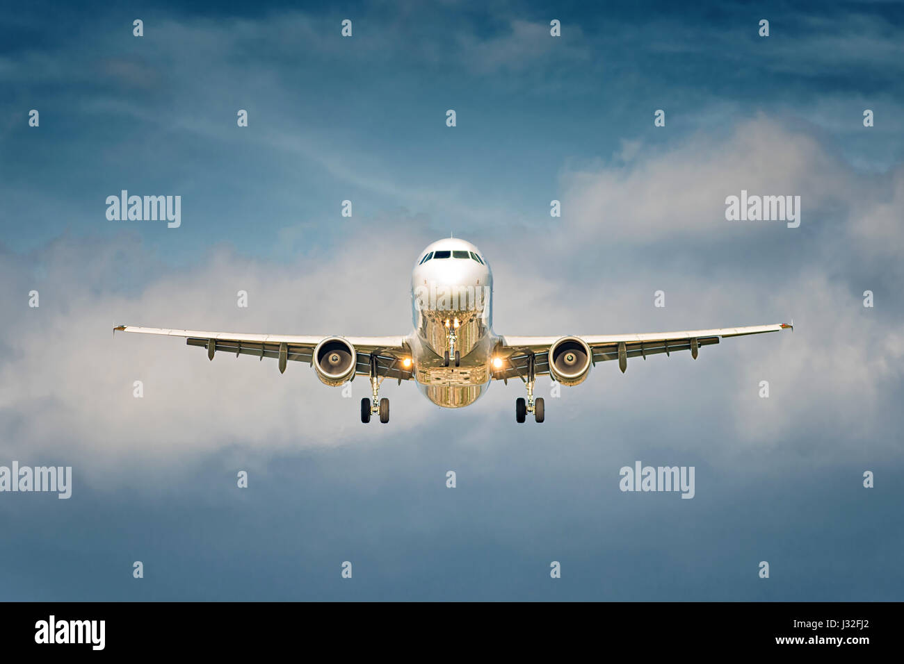 Front view of a big jet plane taking off on blue cloudy sky background Stock Photo