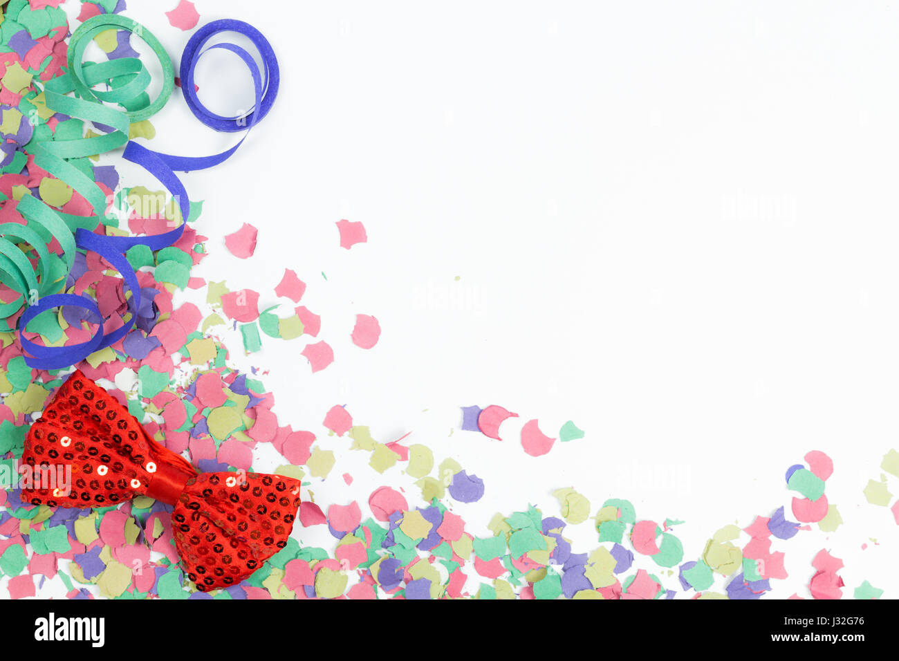 confetti, streamers and red bow on white background - Stock Image