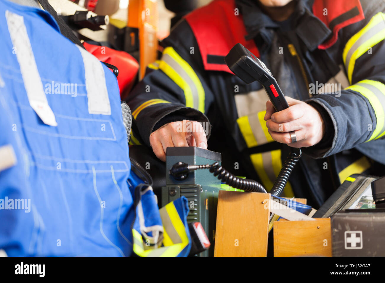 German firefighter drives in a fire truck in action and used a walkie talkie - Stock Image