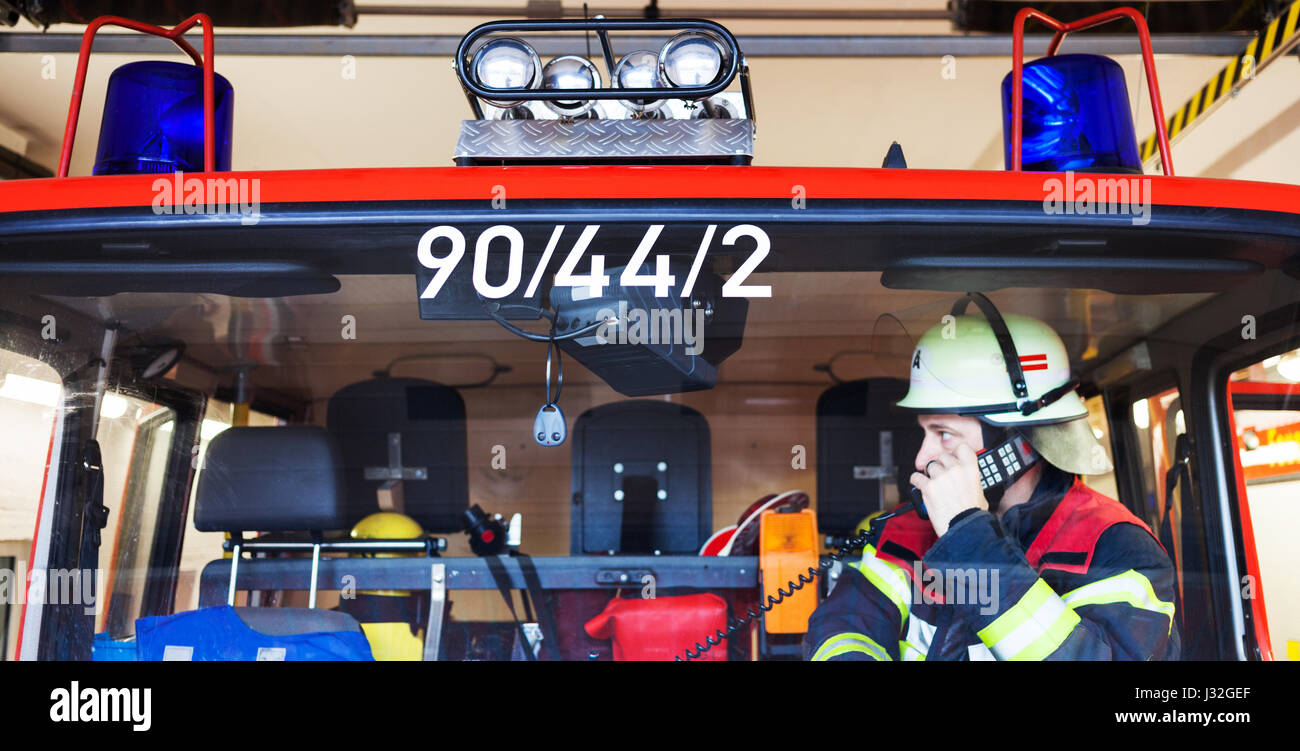 German firefighter in a fire truck with walkie talkie - Stock Image