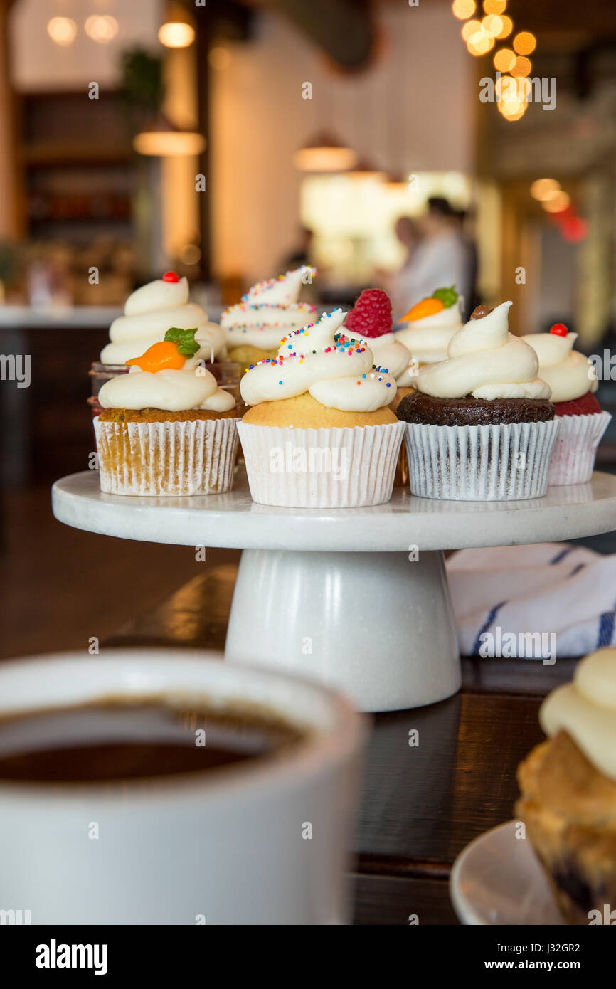 Gourmet assorted cupcakes displayed on a white ceramic cake stand inside a bakery - Stock Image