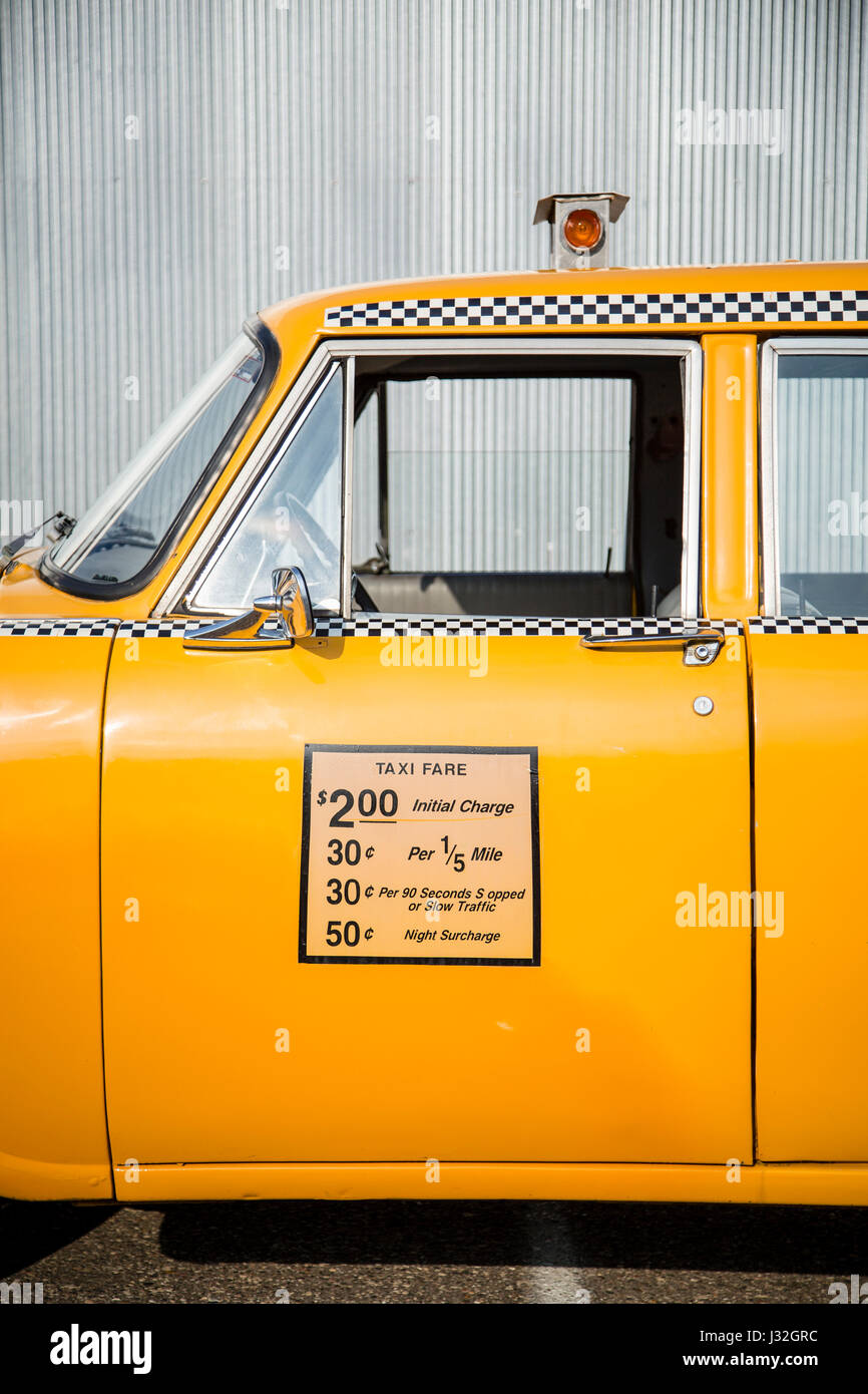 Driver's side view of the middle portion of a vintage yellow checker cab, outlined against a corrugated metal - Stock Image