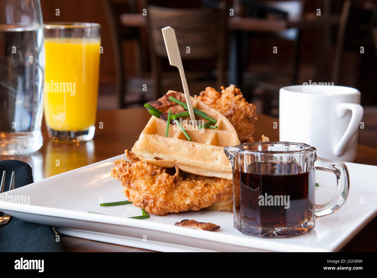 A Southern brunch of fried chicken and waffles at a restaurant - Stock Image