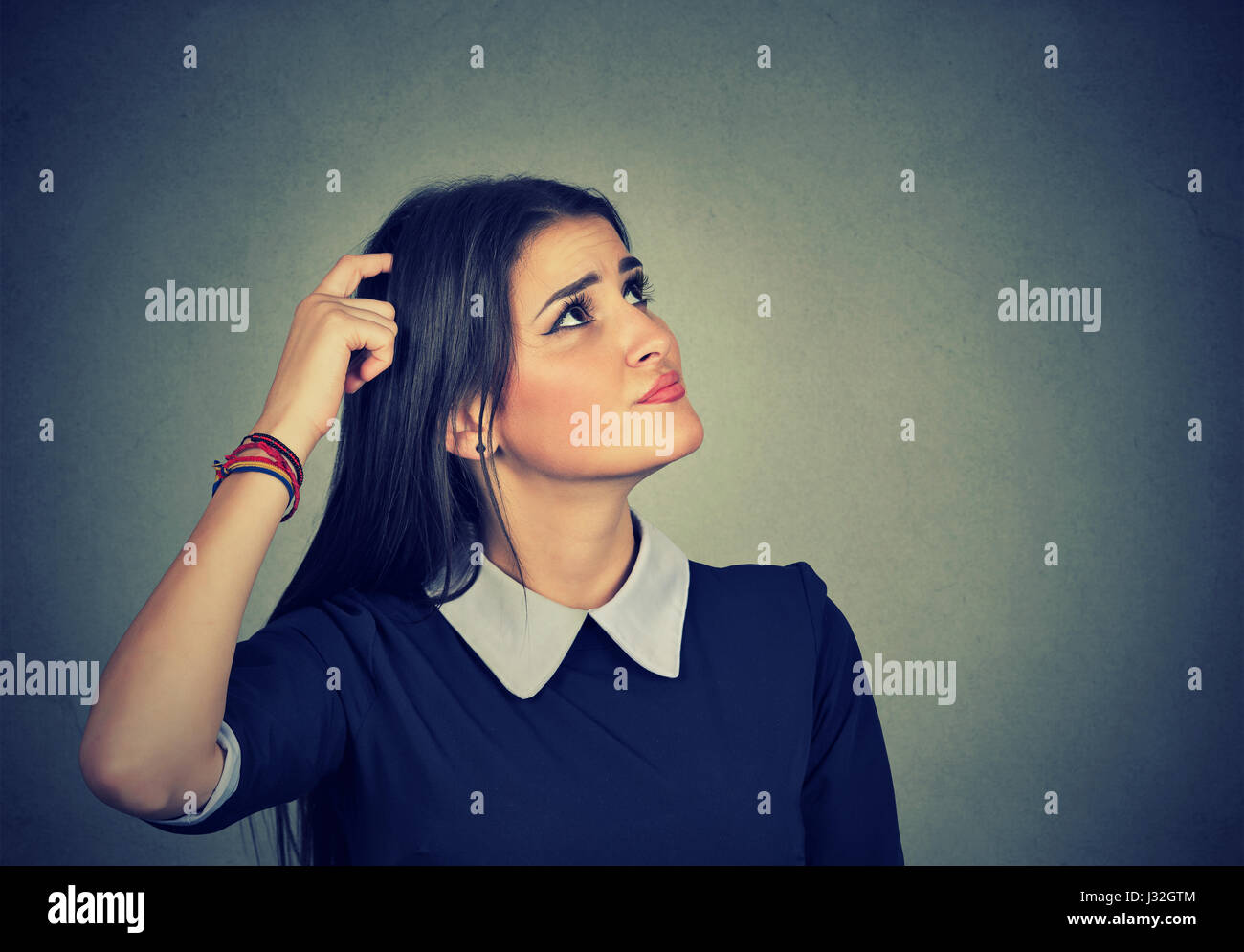 Portrait confused thinking young woman bewildered scratching her head seeks a solution looking up isolated on gray - Stock Image