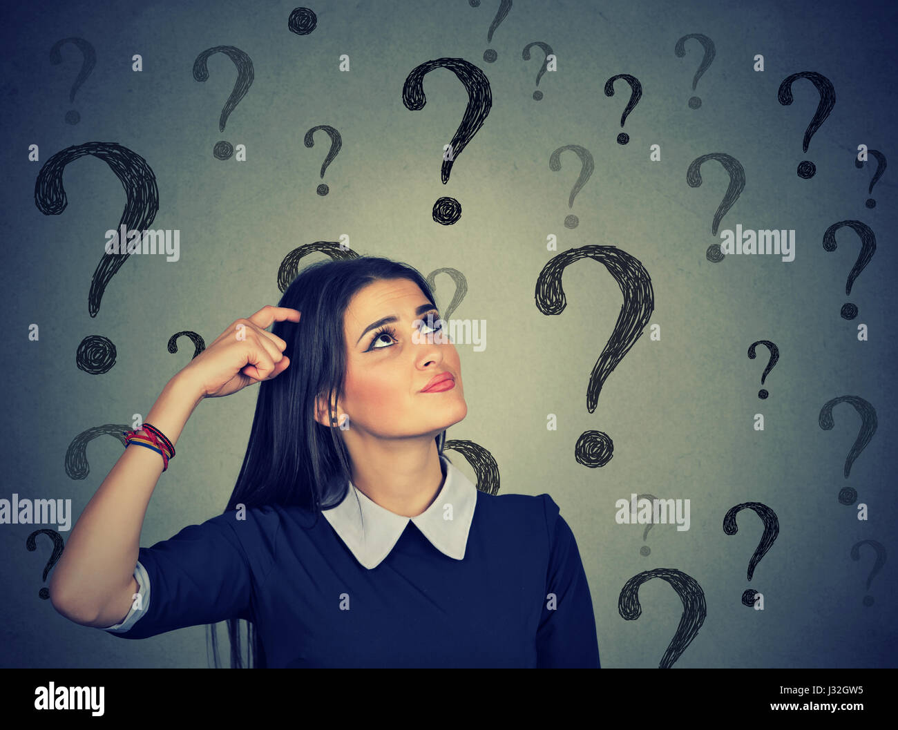 Portrait confused thinking young woman bewildered scratching head seeks a solution looking up at many question marks - Stock Image