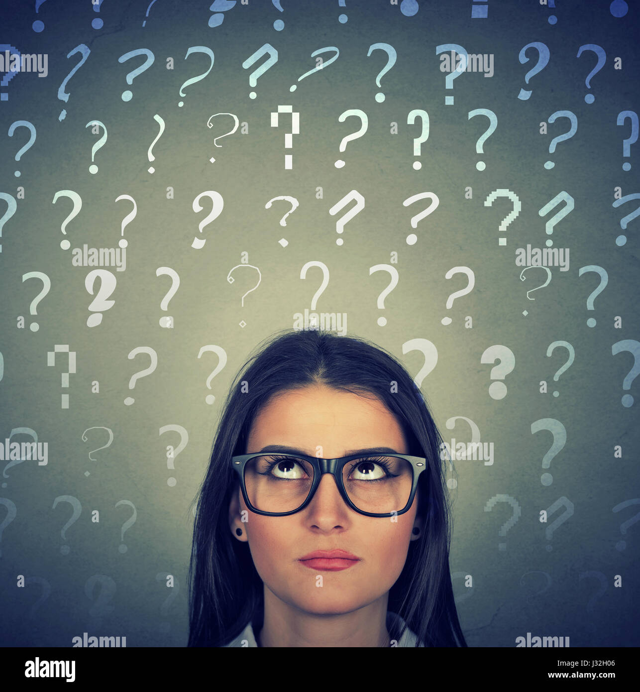 Upset thinking business woman with glasses looking up many question marks above head isolated on gray wall background - Stock Image