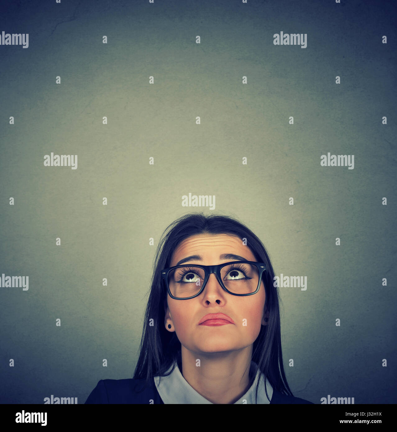 Young skeptical woman looking up isolated on gray wall background with copy space above head. Human emotions, feelings - Stock Image