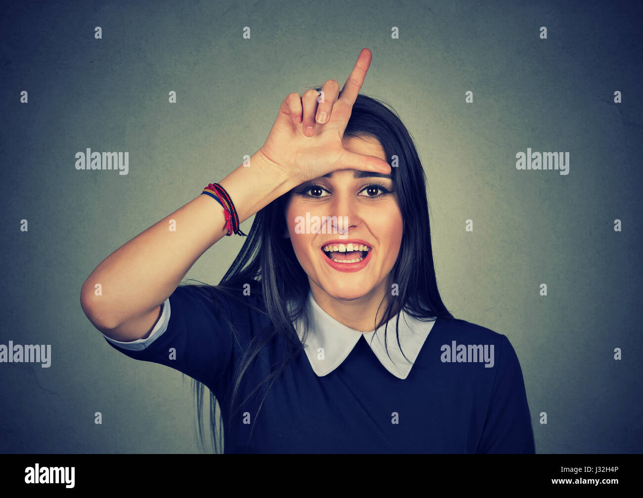 woman giving loser sign looking at you, making fun isolated on gray wall background - Stock Image