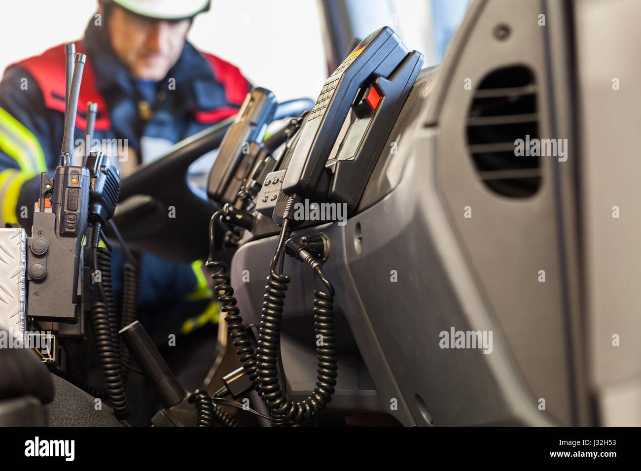 Firefighter drives a emergency vehicle with communication interior view and trowel - Stock Image