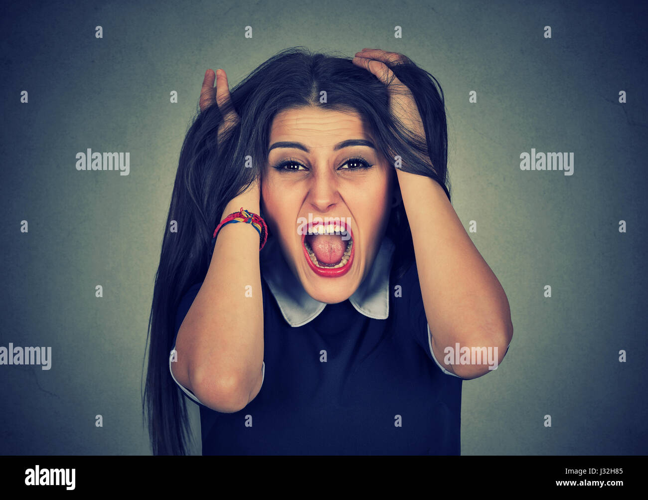 Stressed out young woman pulling her hair - Stock Image