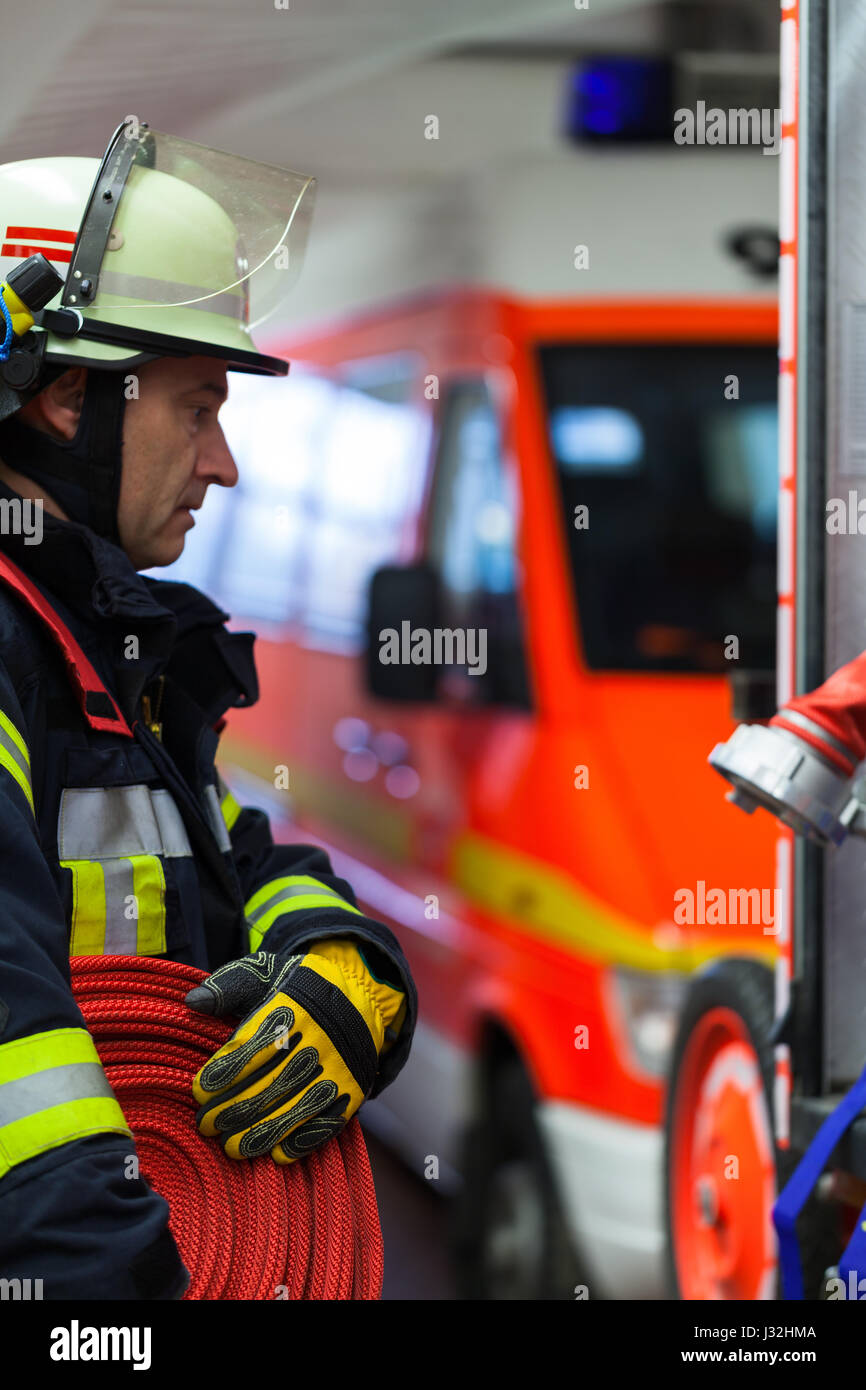 German firefighter in the fire station with a water hose in the hand - Stock Image