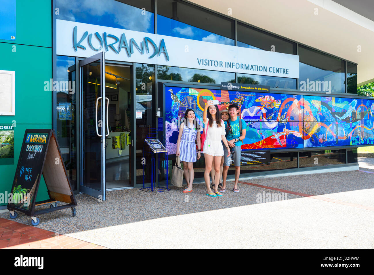 Asian Tourists taking a selfie in front of the Visitor Information Centre in Kuranda Village, Far North Queensland, - Stock Image