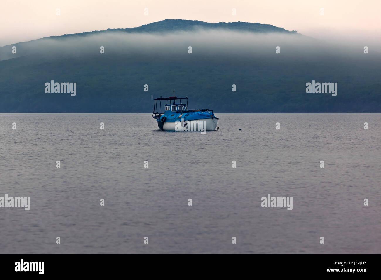 Anchored boat, sopka, misty morning, Vladivostok - Stock Image