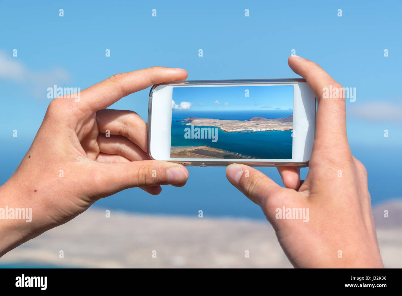Close up on hands holding a smartphone to take pictures, in Lanzarote, Spain - Stock Image
