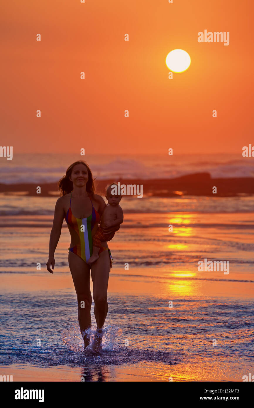 Family swimming fun on black sand beach with sea surf. Happy mother walk with baby son on ocean beach on sunset - Stock Image