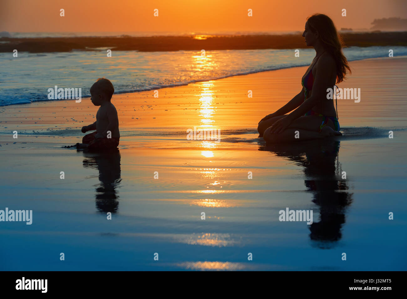 Family swimming fun on black sand beach with sea surf. Happy mother, baby son sit and look at ocean on sunset sky - Stock Image