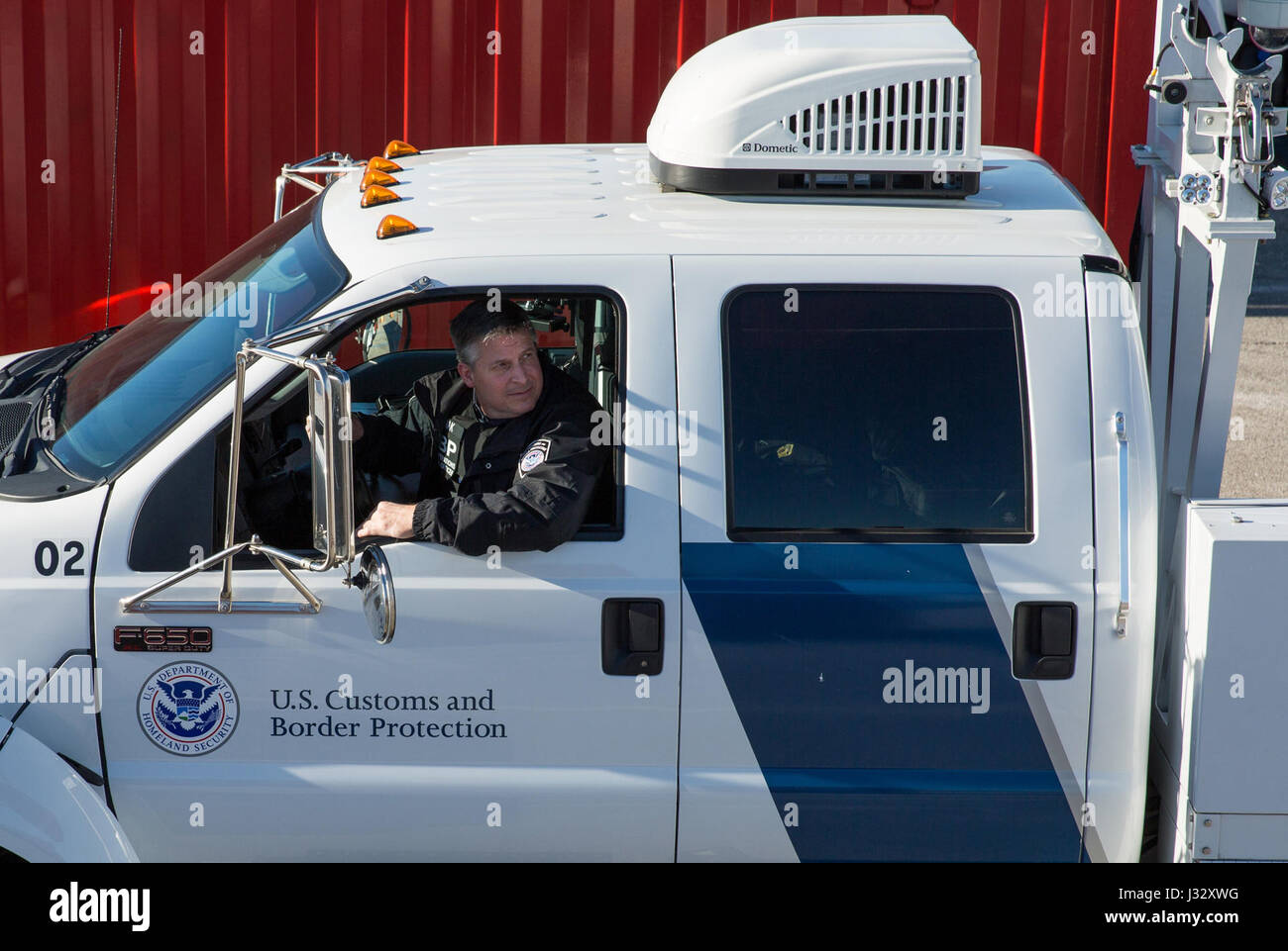 Officers with the U.S. Customs and Border Protection Office of Field Operations conduct inspections of commercial - Stock Image