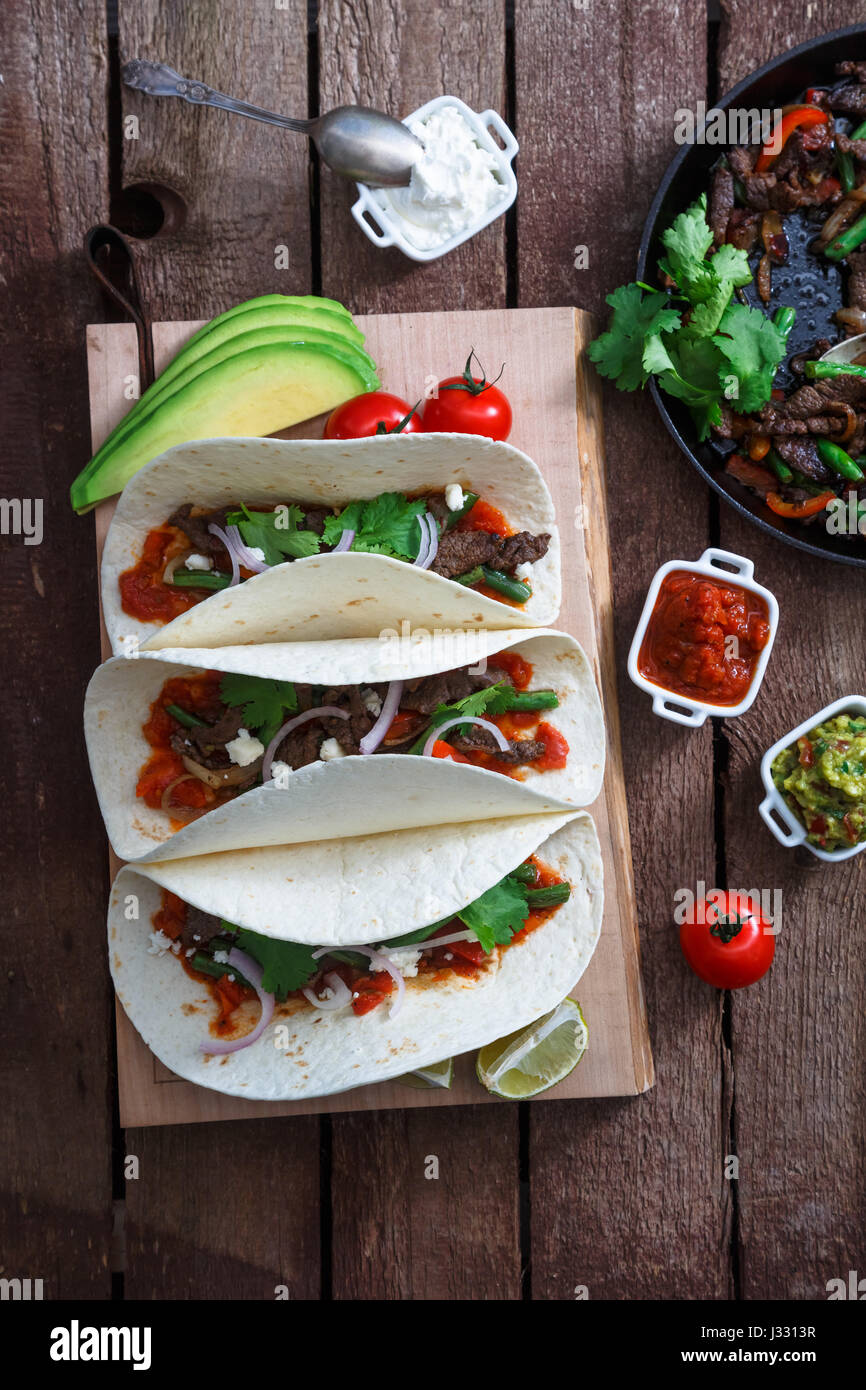 Above view of wheat wraps with mexican pork fajitas, selective focus - Stock Image