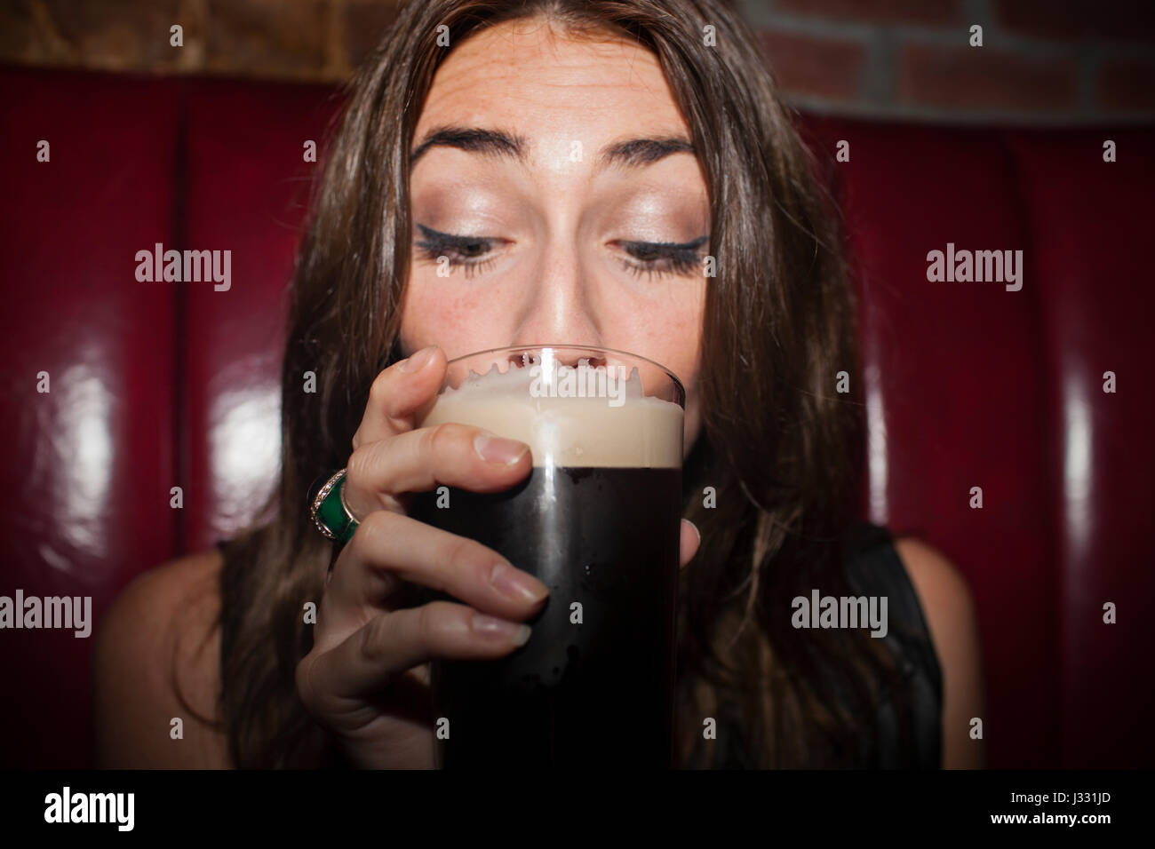 Young woman enjoying a drink - Stock Image