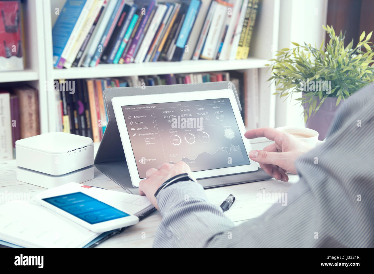 Man uses tablet pc with personal finance manager application. Application made in graphic program - Stock Image
