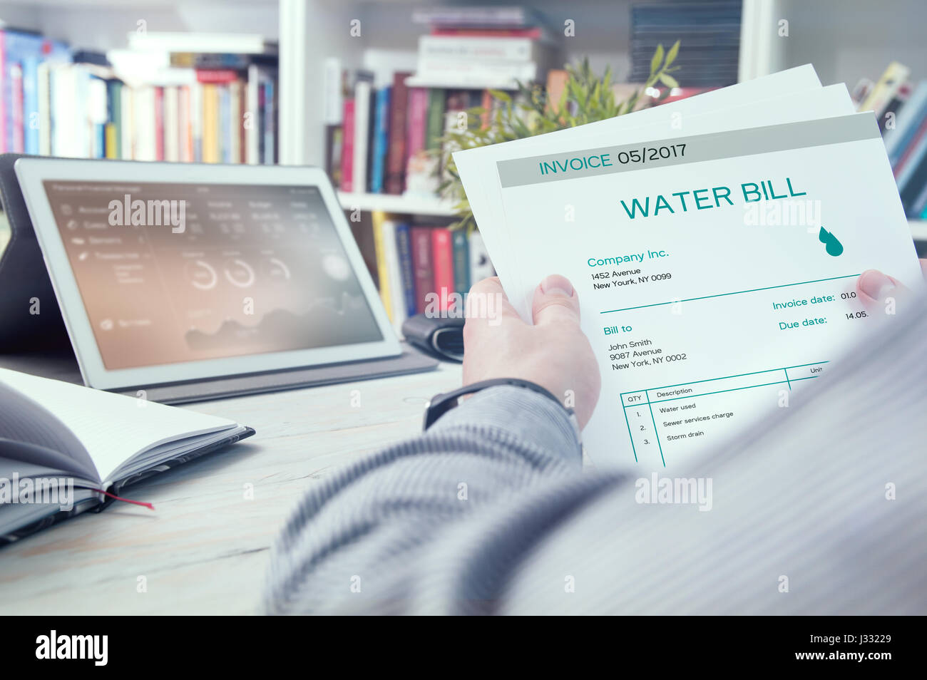 Man holds invoice of water usage - Stock Image