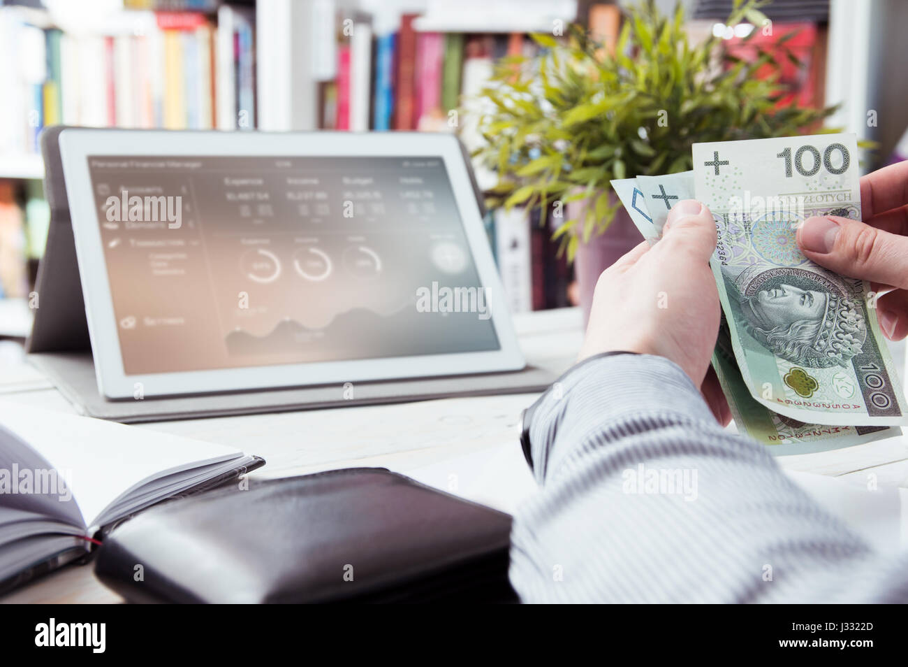 Man holds money. Personal finance manager application in background - Stock Image