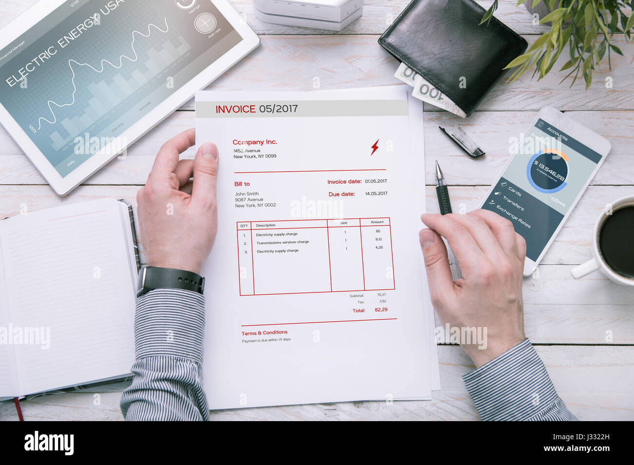 Man holds invoice of electric power usage over desk with tablet and smartphone with applications made in graphic Stock Photo