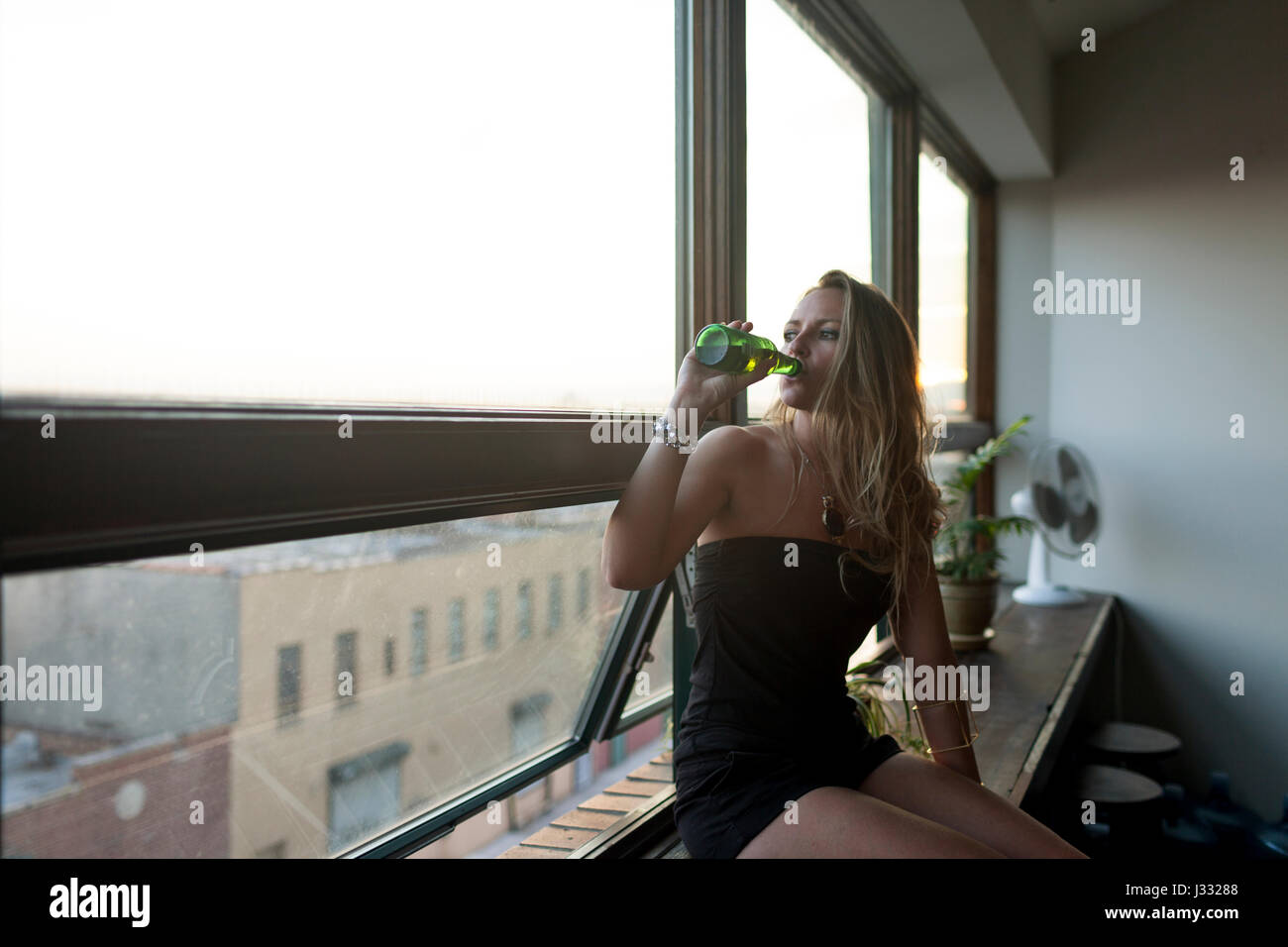 Young woman drinking a beer while looking out a window - Stock Image